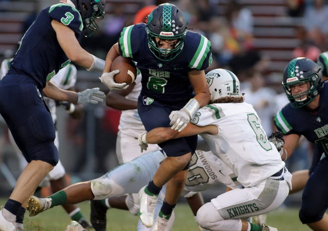 Lukas Merna of Richwoods (6) tries to tackle Peoria Notre Dame running back William Ludolph (8) during Friday night's game at Peoria Stadium.