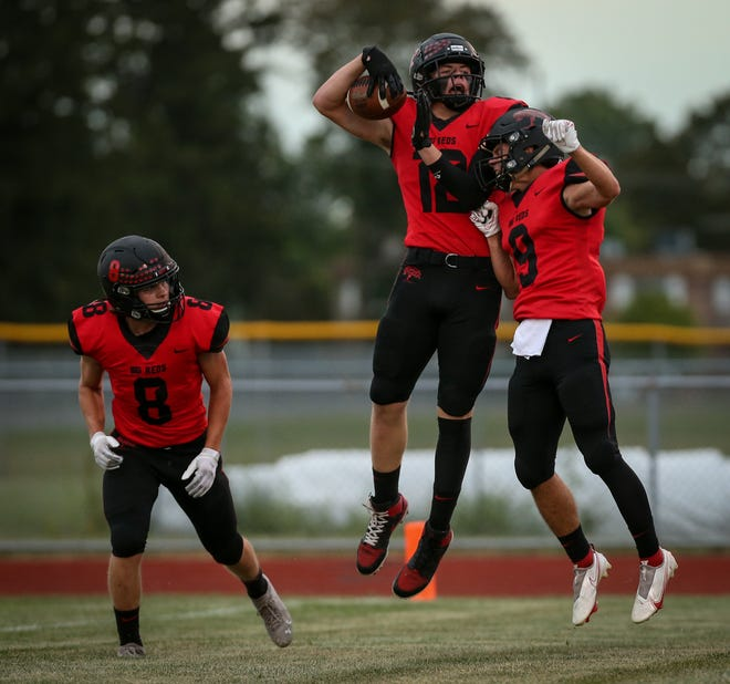 William Gaskell V (12) celebrates the first touchdown Friday evening against New Boston Huron with Carson Baugher (right) and Jett Isaacs.