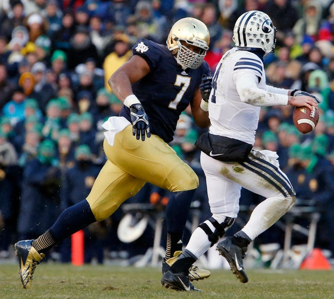 Notre Dame defensive lineman Stephon Tuitt (7) pressures BYU quarterback Taysom Hill (4) during an ND-BYU game on Saturday, Nov. 23, 2013, at Notre Dame Stadium.
