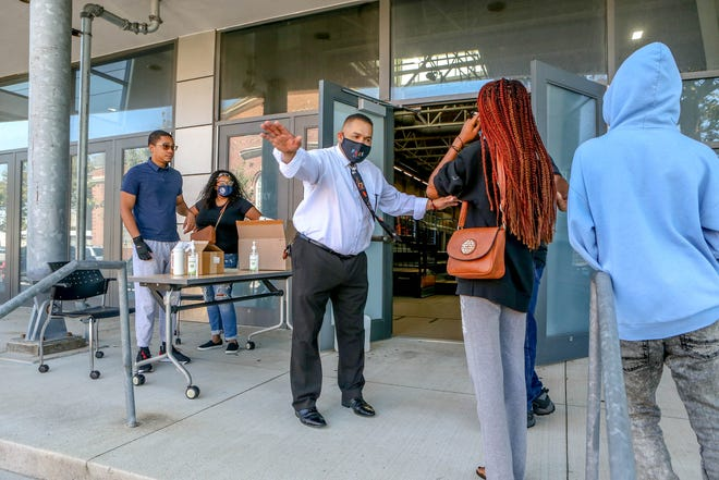 Providence School Supt. Javier Montañez welcomes people arriving for a vaccination clinic on Saturday at Providence Career & Technical Academy.