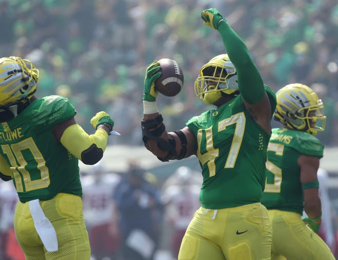 Justin Flowe and Mase Funa celebrate Funa's first-quarter fumble recovery that led to an Oregon touchdown during Saturday's 31-24 win over Fresno State.