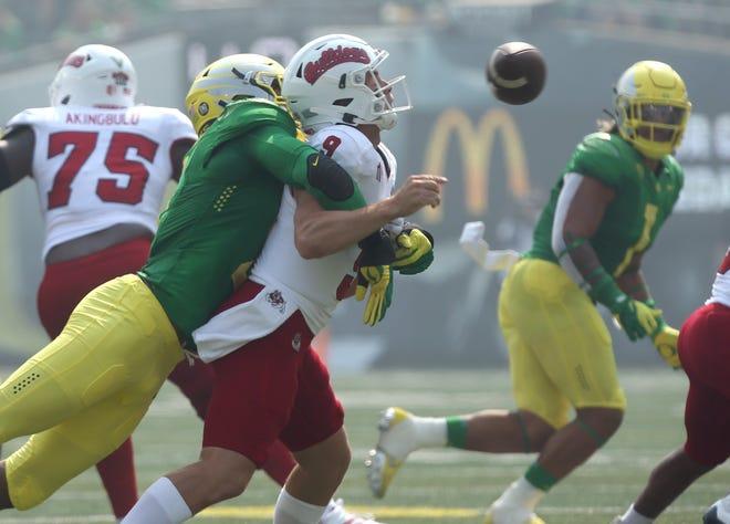 Oregon's Kayvon Thibodeaux, left, sacks Fresno State quarterback Jake Haener forcing a turnover during the first quarter at Autzen.