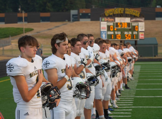 Marist players stand for the national anthem before Friday's football game against Sweet Home.