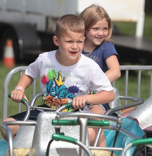 Cousins Trinity Clark, 5, and Rob Hahn, 7, ride the Racing Quads at the Stark County Fair on Saturday, September 4, 2021.