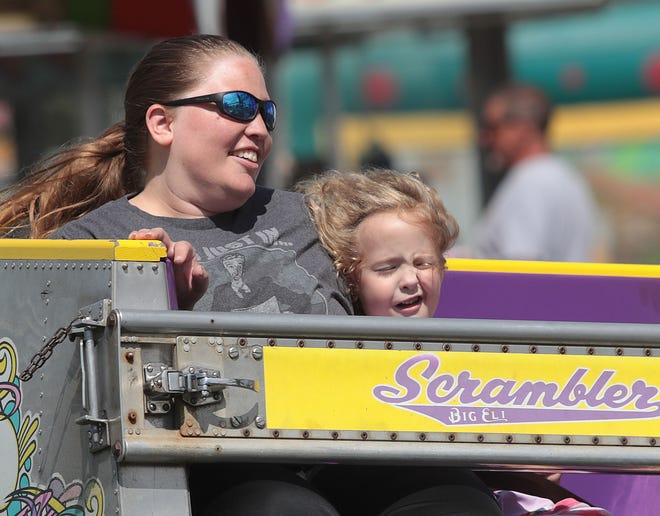 Five-year-old Ady Pettigrew is pushed up against her mother, Katie Pettigrew, while riding the Scrambler at the Stark County Fair on Saturday, September 4 , 2021.