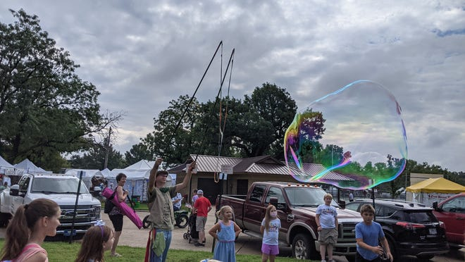 Stephen Treder with Magic Bubbles and Balloons out of San Francisco makes big bubbles in front of a crowd of kids in the Artyopolis neighborhood at the Smoky Hill River Festival. Treder, who went to school in Lindsborg, said the festival is one of his favorite events to perform at.