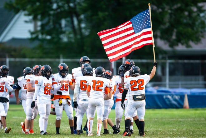 Lanphier's Logan Payne (22) carries the American Flag as he leads the Lions on to the field to take on Springfield at Memorial Stadium in Springfield, Ill., Friday, September 3, 2021. [Justin L. Fowler/The State Journal-Register]