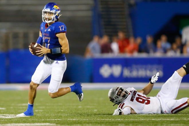 Kansas redshirt junior quarterback Jason Bean escapes a South Dakota player during a play in the first half of Friday's game at David Booth Kansas Memorial Stadium.