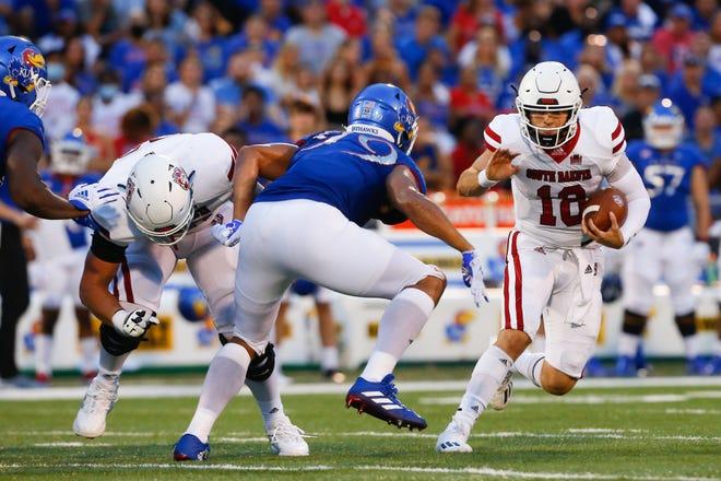 South Dakota freshman quarterback Carson Camp looks for a path around Kansas defensive lineman Malcom Lee in the first half of Friday's game at David Booth Kansas Memorial Stadium.