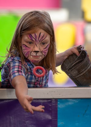 Amelia Collaro, 7, of Spencer plays the ring toss game at the Spencer Fair Saturday. The annual fair runs through Monday.