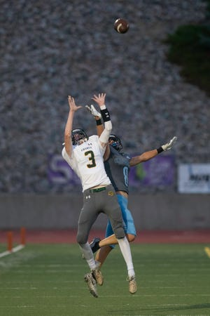 Pueblo County High School's Corbin Spear goes up high on a long pass with a Pueblo West defender providing coverage during the 2021 Pigskin Classic at Dutch Clark Stadium on Friday September 3, 2021.