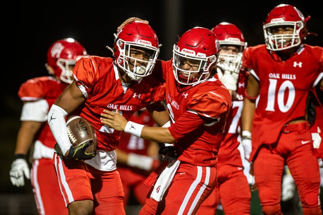 Oak Hills quarterback Andrew Garcia, right, celebrates with Jayon Gillett after throwing a touchdown pass against Palmdale on Sept. 3, 2021. Oak Hills won the game 27-7.