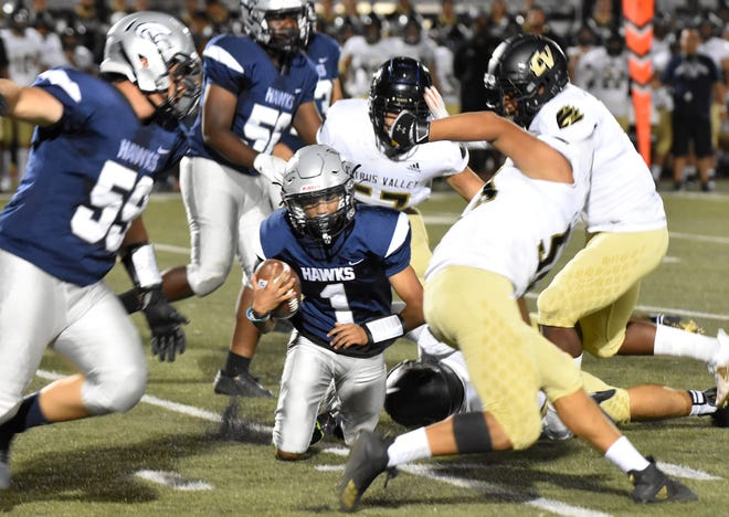 Silverado quarterback Darren Gandy, center, is tripped up by a Citrus Valley defender during the second half on Sept. 3, 2021.