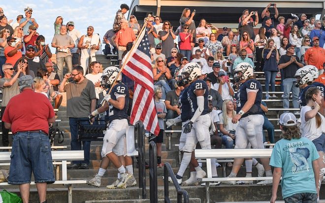 Powdersville junior Luke Hiller(42) carries the United States flag leading teammates through the crowd into the stadium before the game with Wren and Powdersville in Powdersville, S.C. Friday September 3, 2021. Powdersville High School won 10-9.