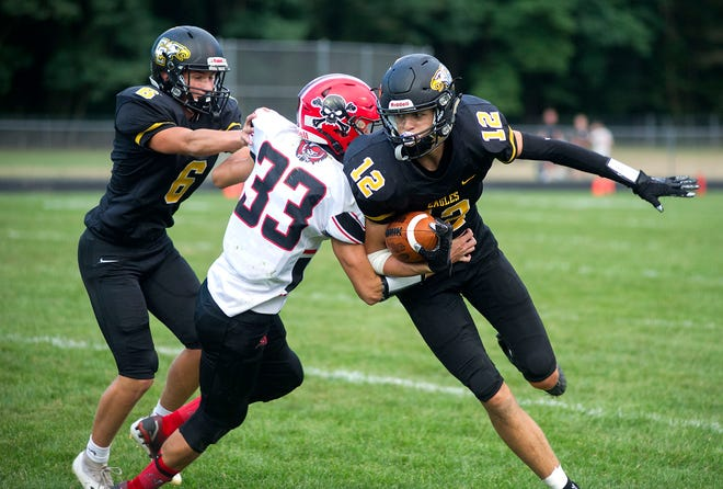 Colonel Crawford's Carter Valentine slips by Cardington's Tyler Rose.