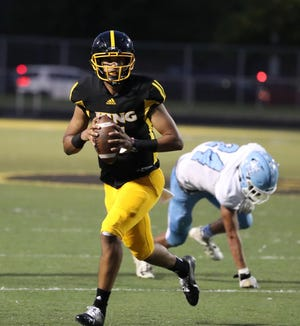 Detroit King's Dante Moore, a Notre Dame recruiting target, gets by Muskegon Mona Shores' Steve Koziak during second-half action at Detroit King High School on Friday, September 3, 2021.