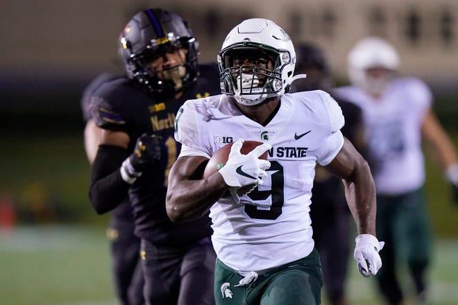 Michigan State running back Kenneth Walker III (9) runs for a touchdown past Northwestern safety Brandon Joseph (16) during the first half of an NCAA college football game in Evanston, Ill., Friday, Sept. 3, 2021.