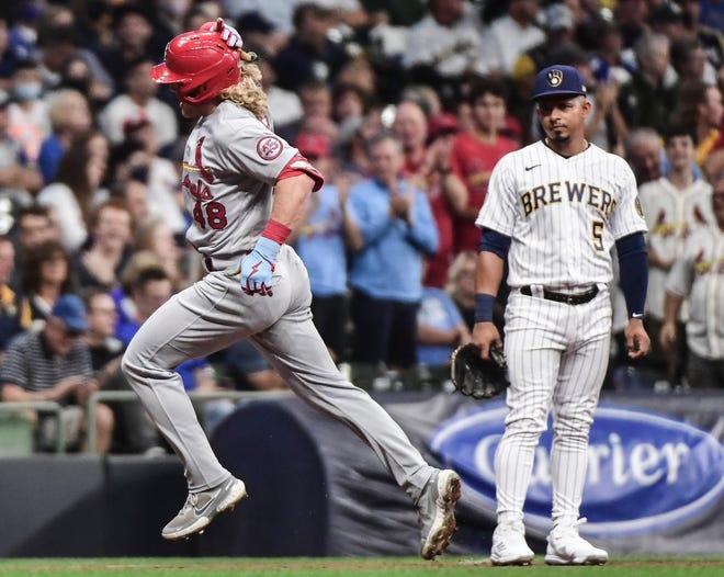 Cardinals center fielder Harrison Bader runs past Brewers third baseman Eduardo Escobar after hitting a three run home run in the third inning Friday night at American Family Field.
