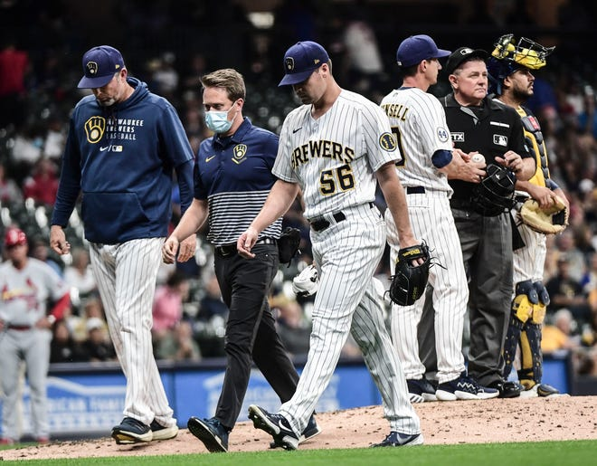 Sep 3, 2021; Milwaukee, Wisconsin, USA; Milwaukee Brewers pitcher Justin Topa (56) leaves the game against the St. Louis Cardinals after suffering an apparent injury in the third inning at American Family Field. Mandatory Credit: Benny Sieu-USA TODAY Sports