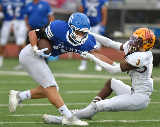 Davison's Henry Carstarphen III, right, brings down Catholic Central's Mike Downs after Downs intercepted a pass intended for Carstarphen.