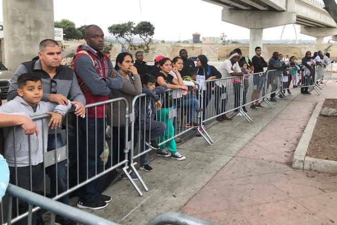 FILE - In this Sept. 26, 2019, file photo asylum seekers in Tijuana, Mexico, listen to names being called from a waiting list to claim asylum at a border crossing in San Diego. A federal judge ruled Thursday, Sept. 2, 2021 that the U.S. government's practice of denying migrants a chance to apply for asylum on the Mexican border until space opens up to process claims is unconstitutional.(AP Photo/Elliot Spagat, File)