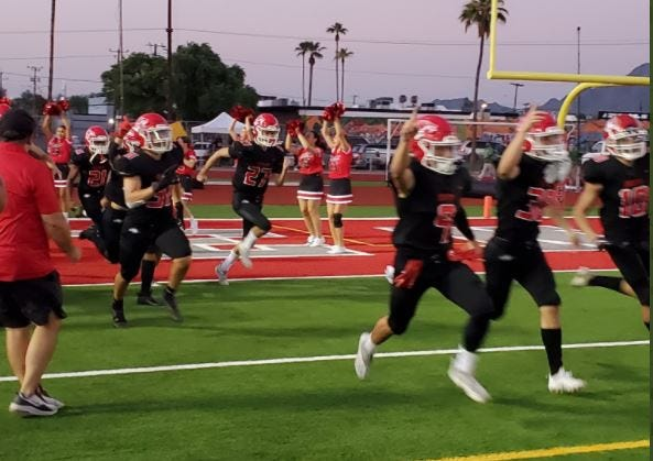 Brophy Prep's football team takes the field ahead of its game against St. Mary's at Central High School's field Friday, Sept. 2, 2021.