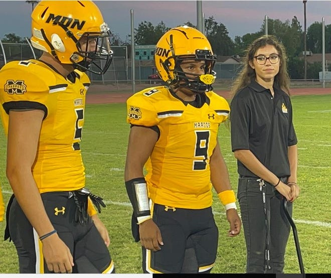 Krysten Muir, right), stands alongside members of the Marcos de Niza football team as they participate in the coin toss before their game against Apache Junction Friday. Sept. 3, 2021.