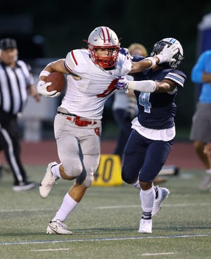 Canandaigua's Elliott Morgan stiff arms Eastridge's Emmanuel Torres to gain a little more yardage at the end of a run.