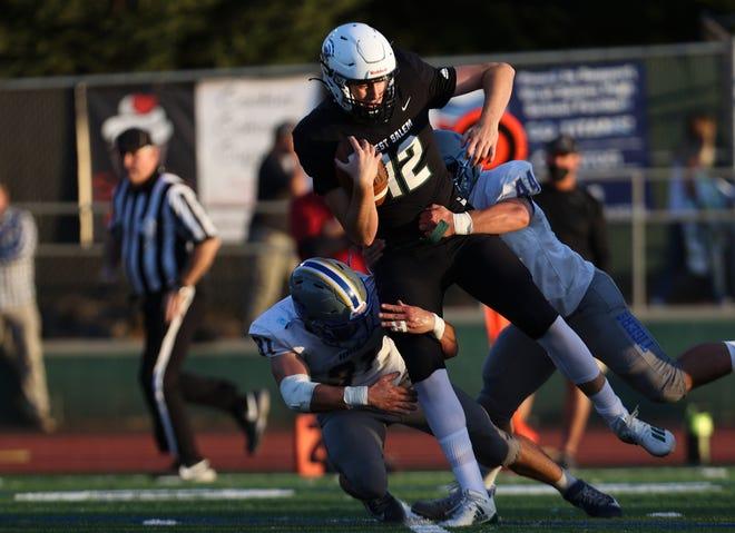 West Salem's Brooks Ferguson (12) is tackled by Newberg's Daniel Valdez-Espinoza (27) and Newberg's Hudson Davis (44) during the first quarter of the game at West Salem High School in Salem, Ore. on Friday, Sept. 3, 2021.