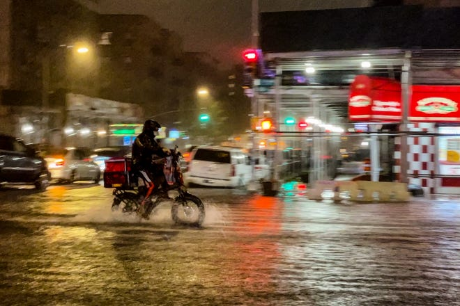 A delivery clerk makes his way in the rain from Hurricane Ida during a flood on Intervale Avenue on September 1, 2021.