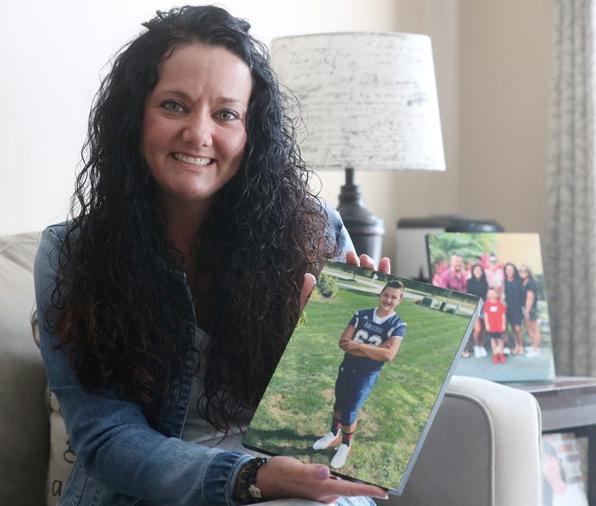 Jody Rearick holds a photo of her son Bryan, 14, who is a student St. Vincent-St. Mary High School, at her home in Tallmadge. Rearick was dismayed to find out that a national pharmacy was requiring her son instead of her to schedule the teen's COVID-19 test.