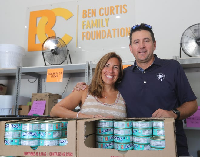 """Candace and Ben Curtis on Aug. 24 at their warehouse in Brady Lake, where volunteers help pack thousands of """"birdie bags"""" to feed hungry schoolchildren."""