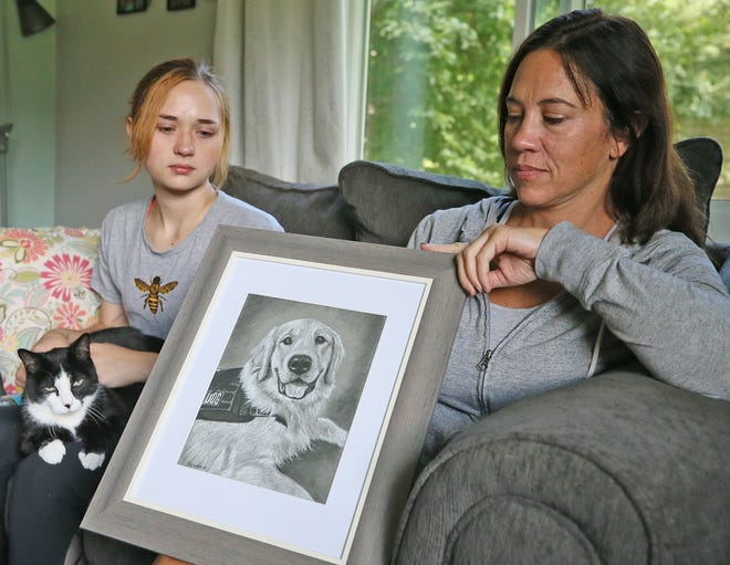 Grace Kolich holds the family cat, Juice, as her mother, Krista Kolich, shows a picture of Benny, Grace's service dog, who they believe died while in the care of a trainer.