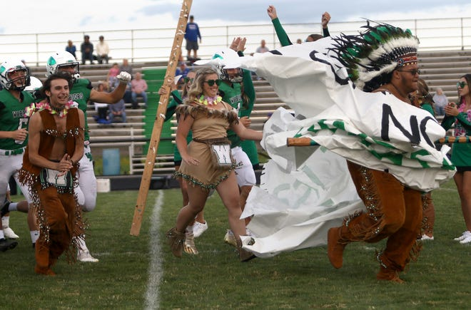 Warrior chief Scott Gallagher, right, assistant chief Cole Butcher, far left, and princess Mayze Leask, center, lead the West Branch football team onto the field Friday, Sept. 3, 2021, against Revere