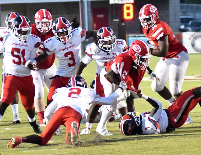Hephzibah's Demetrius Williams (2) and Dwight Tarver Jr. (7) each cling to the fabric of Gamecock running back Isaiah Chappel's jersey as the Screven County sophomore searches for extra yardage on the ground. SCHS fell just short in its season-opening game on Sept. 3 as the Rebels scored in the last 12 seconds for a 30-28 win in Sylvania.