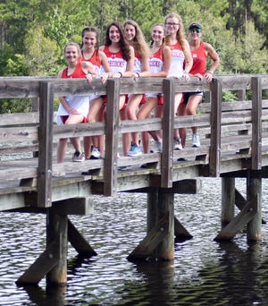 The Lady Gamecock cross country team runs its home meets at the Black Creek Scout Reservation on Poor Robin Road in Sylvania. Part of the 3.1-mile 5K course is a bridge that goes across the 45-acre Eagle Lake on the property. Standing on the bridge are junior Lynnlie Rountree, junior varsity eighth grader Adi Rountree, junior Erin Thompson, sophomore Ashley Langley, junior Mazlin Blessing, Emily Lariscy and head coach Anna Canetto. Pictured in the inset is team member junior Marly Moore.