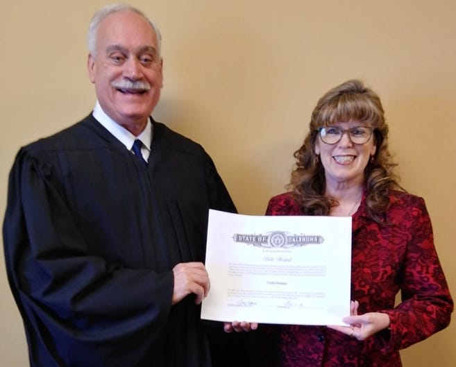 Belle Westfall receiving her Basic Mediation Certification Certificate from Judge David Smith.
