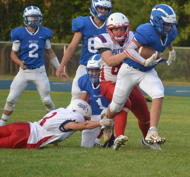 Inland Lakes freshman running back Mitchell Crawford attempts to break a tackle against multiple Charlton Heston Academy defenders in Indian River on Thursday, Sept. 2.