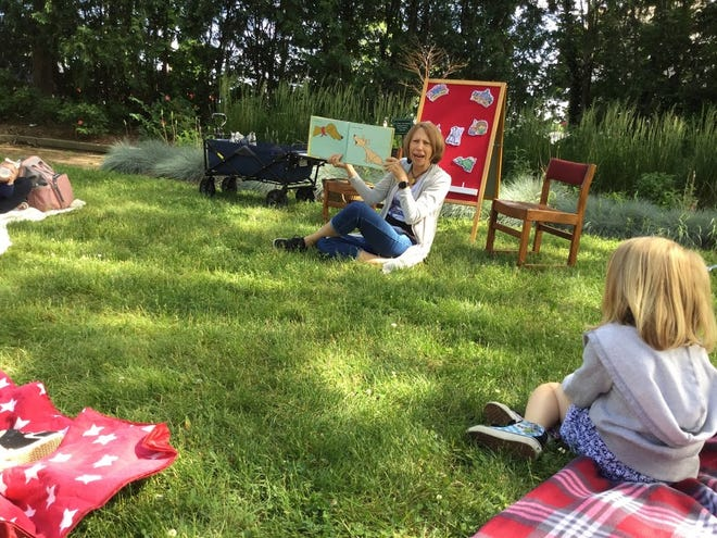 Cathy Chesher, Adrian District Library's youth services librarian, reads to youth during this summer's storytime programming held in Library Square. Chesher and the library will bring more storytime programs back to the Library Square this fall.