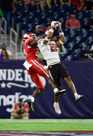 Texas Tech safety Reggie Pearson (22) intercepts a pass intended for Houston wide receiver KeSean Carter during the first half of the Red Raiders' 38-21 victory Saturday. On Monday, Pearson was named the Big 12 newcomer of the week. The transfer from Wisconsin had eight tackles and a forced fumble in addition to the interception.
