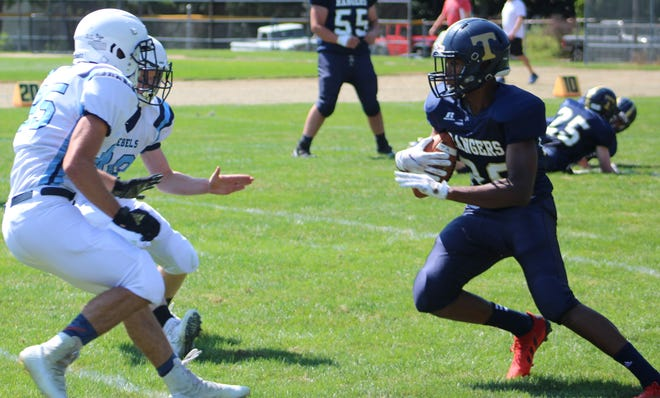 A pair of Telstar defenders close in on Traip's Omar Dovesi during the first quarter of Saturday's season-opening game at Memorial Field in Kittery, Maine. Dovesi is an Italian foreign-exchange who never played football until this summer.