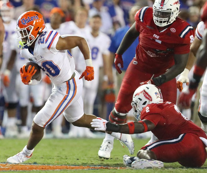 Florida running back Malik Davis escapes a Florida Atlantic defender Saturday at Ben Hill Griffin Stadium.