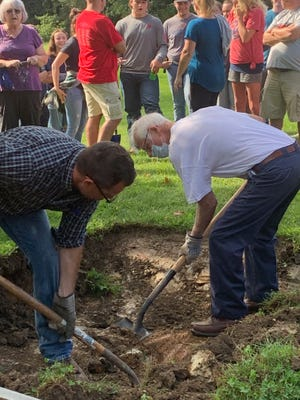 Chris Kimble (left) and Rod Wilson dig up the time capsule.