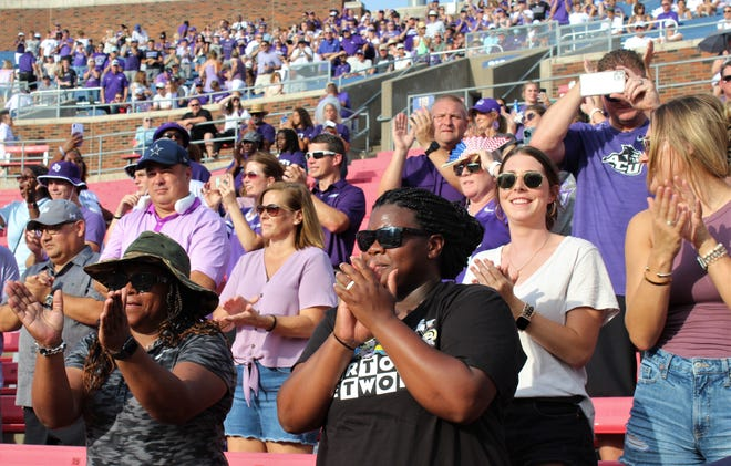 Sherry Donald, right, and her cousin Charise Hamilton join other ACU fans in cheering the arrival of the Wildcats football team onto the field at Ford Stadium in Dallas on Saturday. Donald's son Dimitri is tight ends coach for ACU.