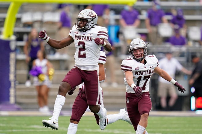 Montana's Gavin Robertson (2) leaps in celebration after making an interception against Washington as teammate Robby Hauck follows in the first half of an NCAA college football game Saturday, Sept. 4, 2021, in Seattle. (AP Photo/Elaine Thompson)