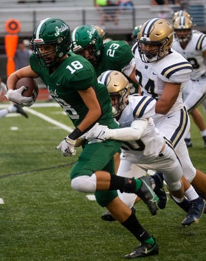 Fisher Catholic's Jack Carpenter (18) drives his way through the Portsmouth Notre Dame defense as Fisher Catholic hosted Portsmouth Notre Dame in high school football action at Fulton Field in Lancaster, Ohio on September 4, 2021.