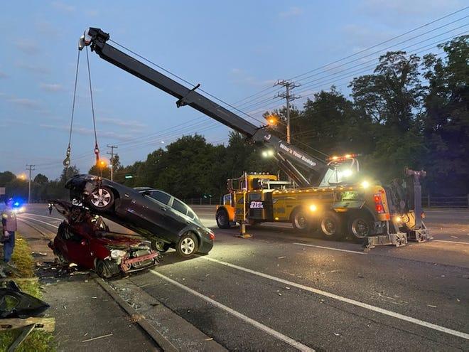 A crew pulls a BMW off a Mitsubishi Mirage after a Saturday morning crash.