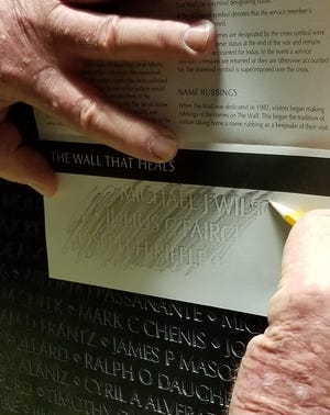 A visitor to The Wall That Heals makes a rubbing of a name from the replica of the Vietnam Veterans Memorial in this undated photo.