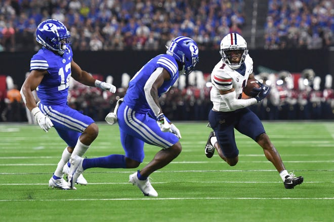 Arizona wide receiver Stanley Berryhill III carries agains the defense of BYU's Malik Moore (12) and D'Angelo Mandell during the first half of an NCAA college football game Saturday, Sept. 4, 2021, in Las Vegas. (AP Photo/David Becker)