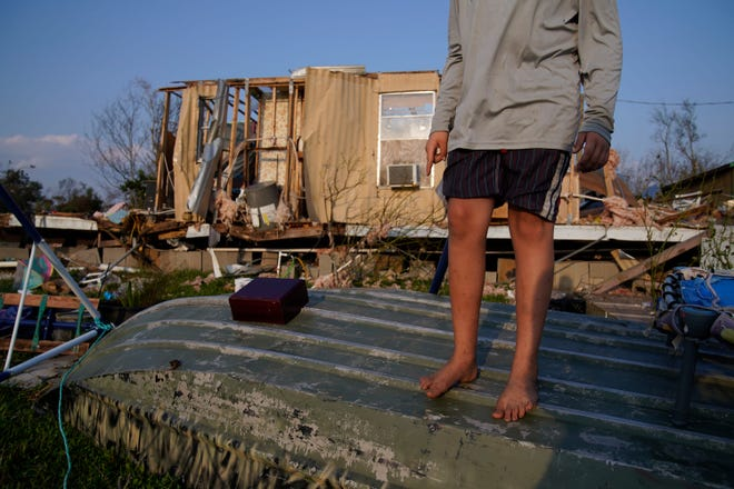 Aiden Locobon stands on a boat near the remnants of his family's home destroyed by Hurricane Ida, Saturday, Sept. 4, 2021, in Dulac, La.